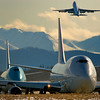 A Southern Air 747-300 waits along with a Korean Air 747-400F for a final u-turn to takeoff at Ted Stevens Intl Airport in Anchorage. Chugach mountains in the backround.