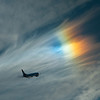 The sun rainbows the thin, high clouds while LOT Airlines 737 departs Heathrow.